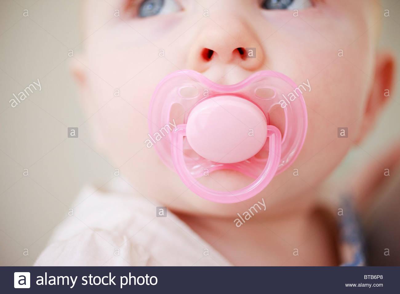 Chiusura del bambino con succhietto rosa Immagini Stock