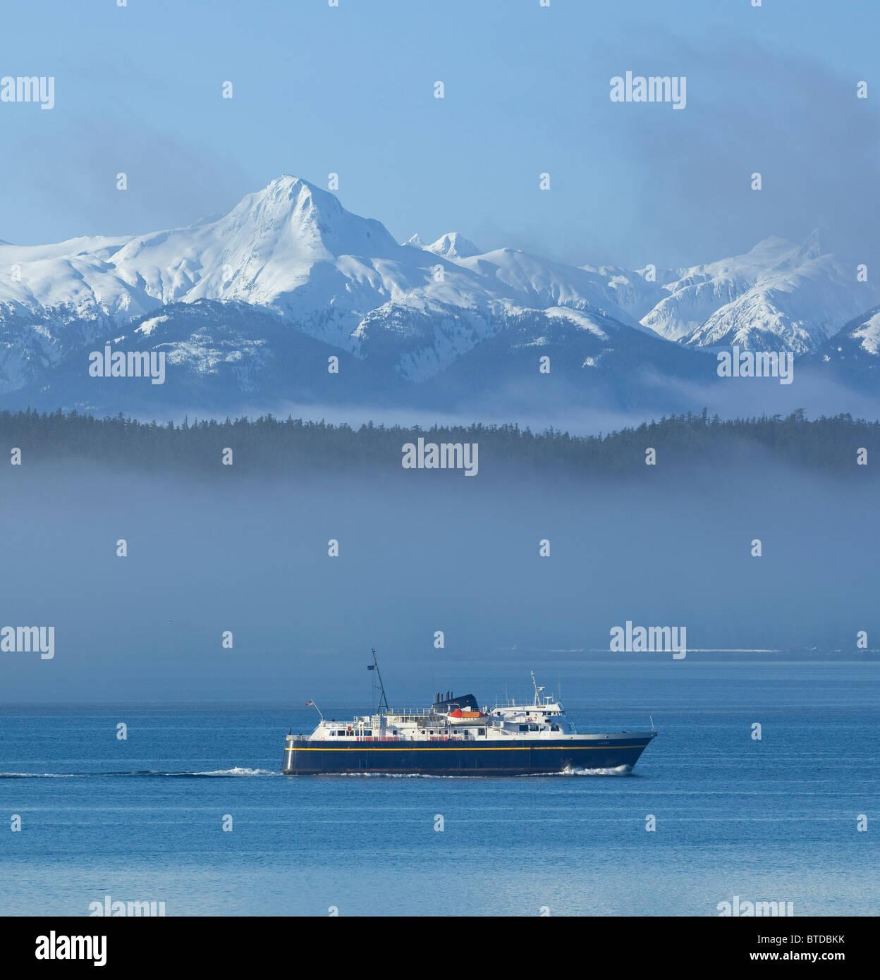 Alaska Marine Highway crociere in traghetto attraverso la nebbia, all'interno di passaggio con picchi snowcovered Immagini Stock