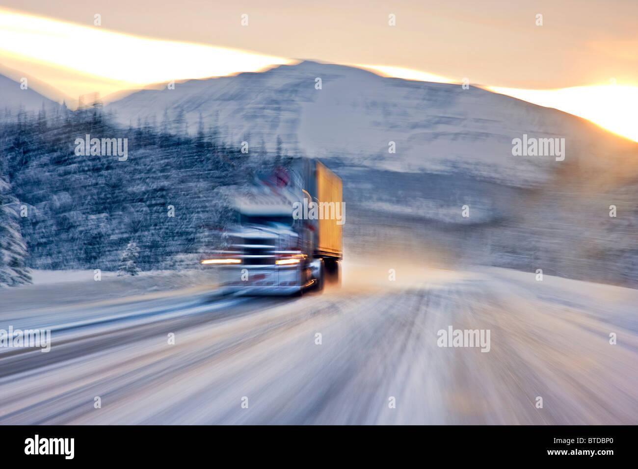 Semi carrello guida su snowcovered Seward Highway presso sunrise, centromeridionale Alaska, inverno Foto Stock