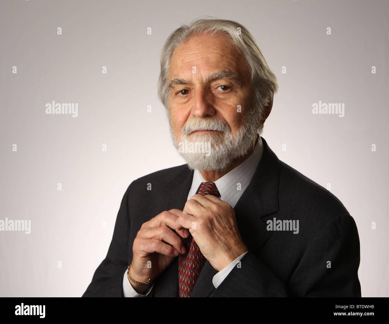 Ritratto di barba e capelli grigi imprenditore senior regolando la cravatta, studio shot, bianco, grigio, 16 Ottobre Immagini Stock