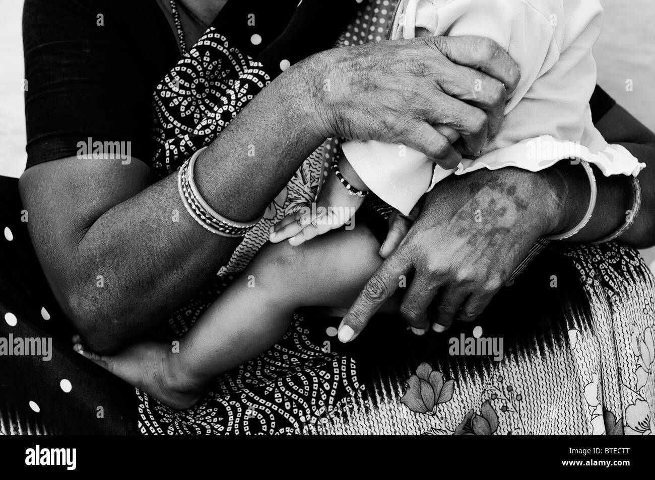 Nonna indiano mani e neonati a piedi nudi. Andhra Pradesh, India. Monocromatico Immagini Stock