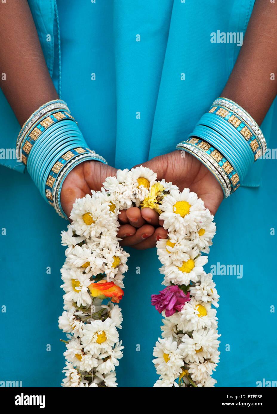 Giovani indiani ragazza con una ghirlanda di fiori dietro la schiena. India Immagini Stock