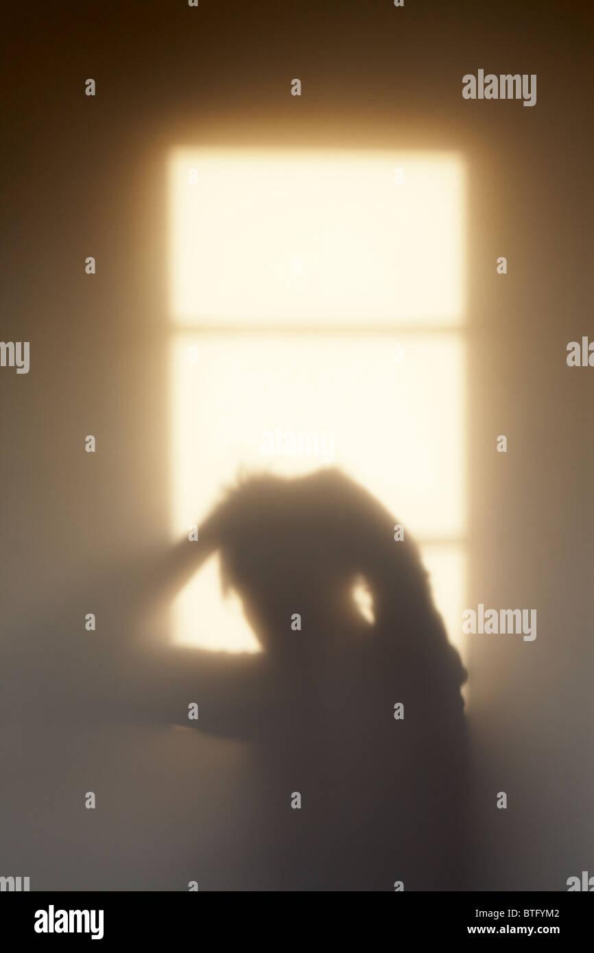 Ombra di una donna la sensazione di pressione, o eventualmente, solo un altro brutto giorno capelli? Immagini Stock