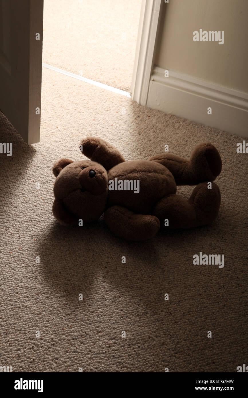 Per bambini orsacchiotto giacente sul piano di un pavimento in moquette come un uomo di piedi in fase attraverso Immagini Stock