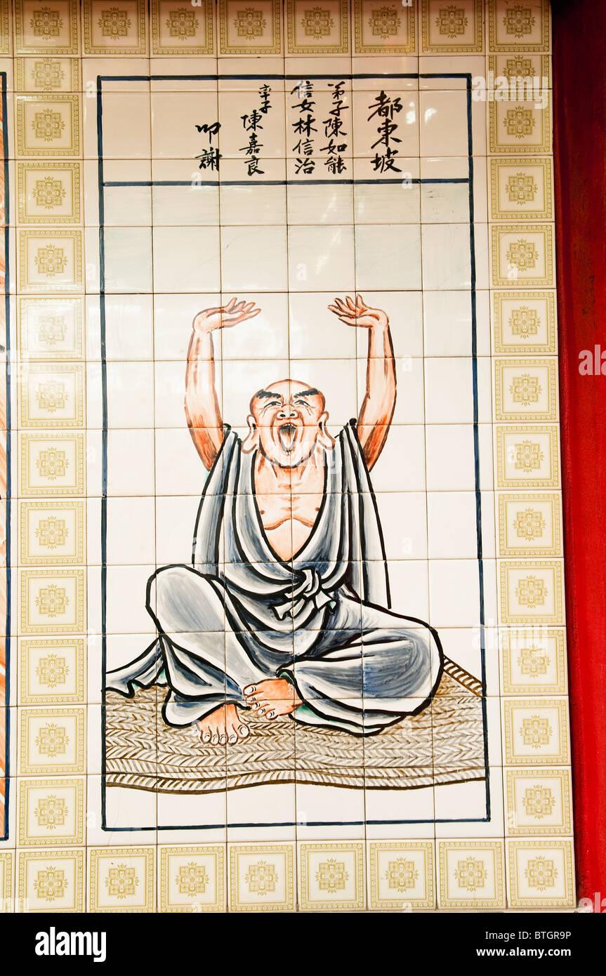 Dipinto piastrelle pannello nel tempio Cinese in Bandar Seri Begawan di un vecchio uomo di stretching e sbadigli. Immagini Stock