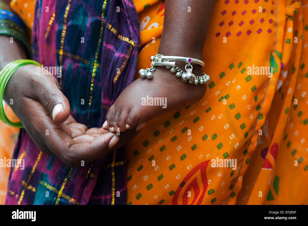 Bambini indiani piedi nudi contro le madri vestiti colorati. India Immagini Stock