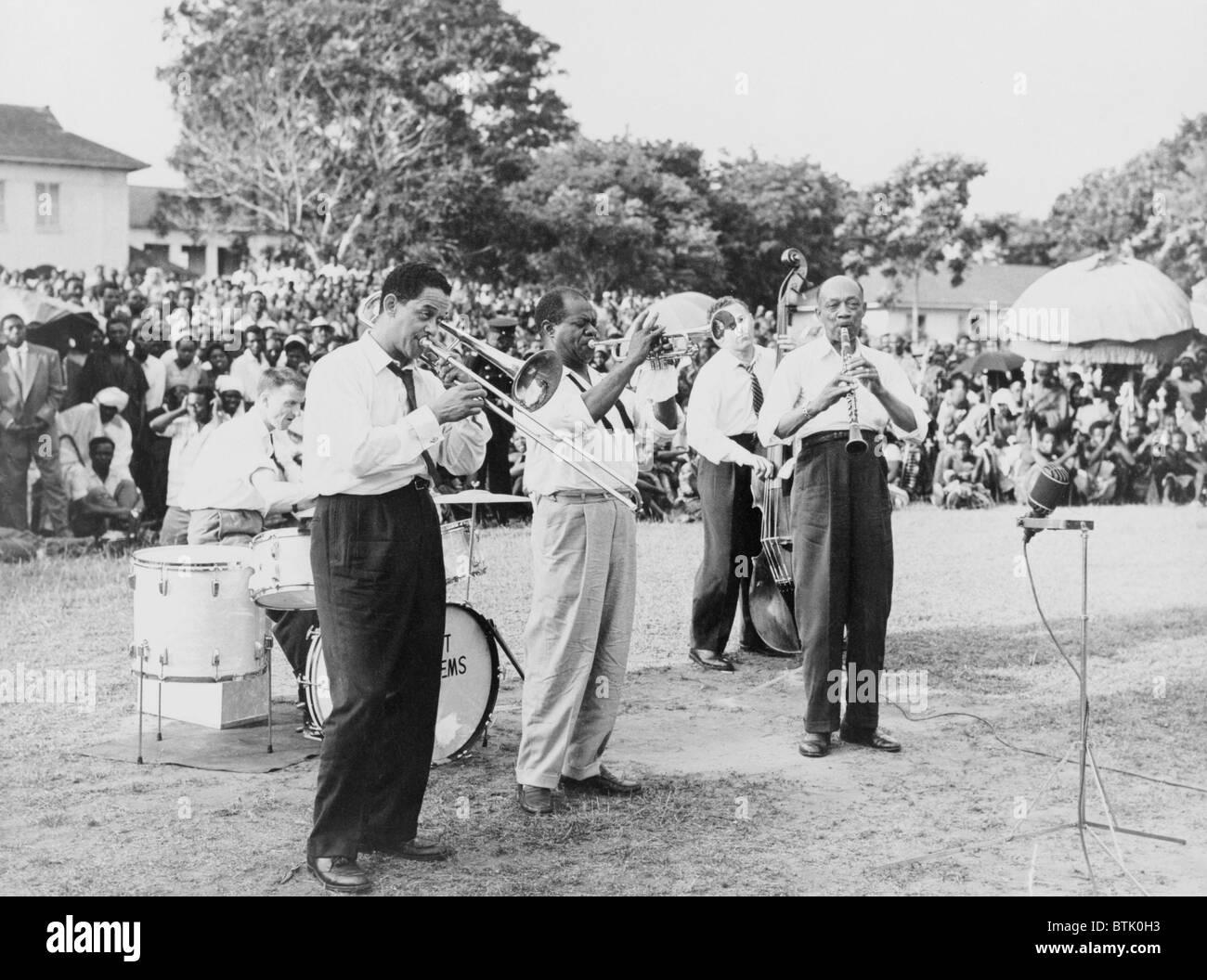 Louis Armstrong (1901-1971), African American musicista jazz, suonare la tromba con banda a un raduno per esterni in Africa, 1956. Foto Stock