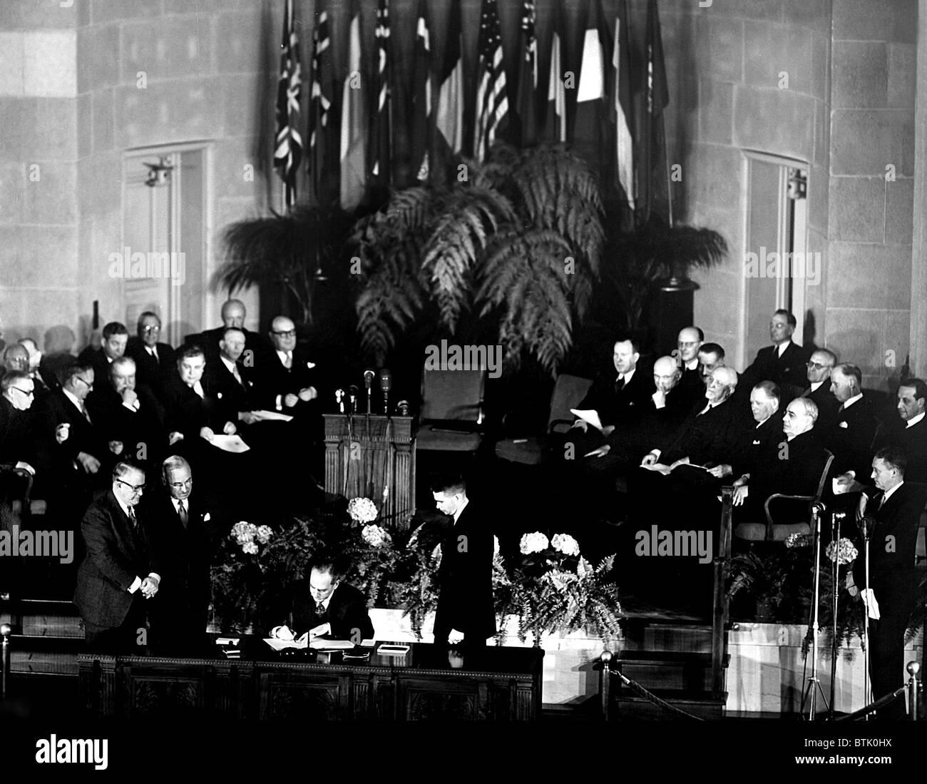 La NATO, il Presidente Truman e V.P. Barkley, guarda su come Segretario di Stato Dean Acheson firma il Trattato Immagini Stock