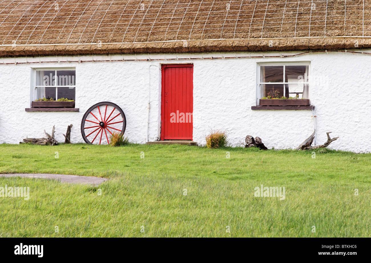 Un cottage con tetto di paglia con una porta rossa a Glencolmcille Folk Village, County Donegall, Ulster, Eire. Immagini Stock