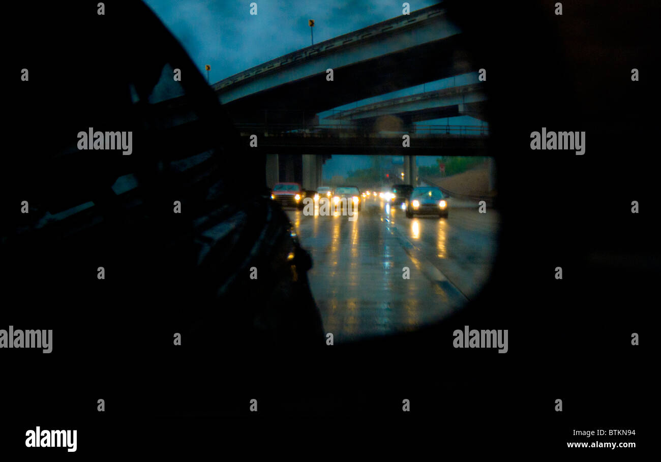 Il traffico di Freeway riflessa in auto specchio retrovisore durante la pioggia torrenziale storm in Houston, Texas, Immagini Stock