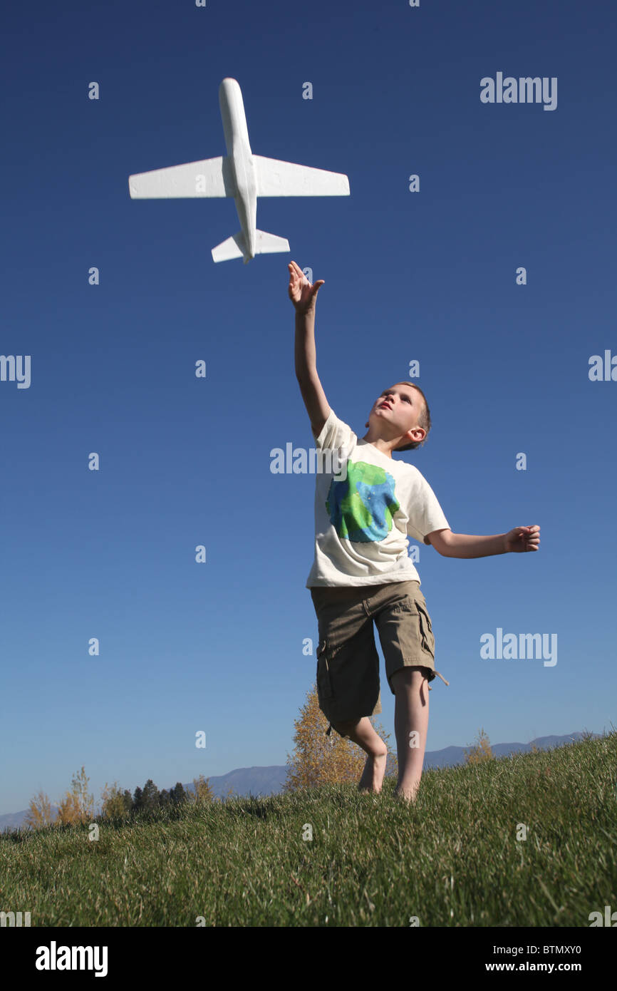 Oung yhappy boy gettando aeroplano giocattolo in aria Immagini Stock