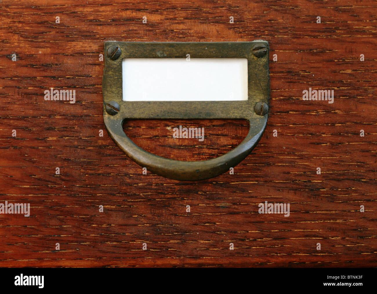 Il legno vecchio catalogo a schede con cassetto vuoto etichetta bianca e tirare in ottone Immagini Stock