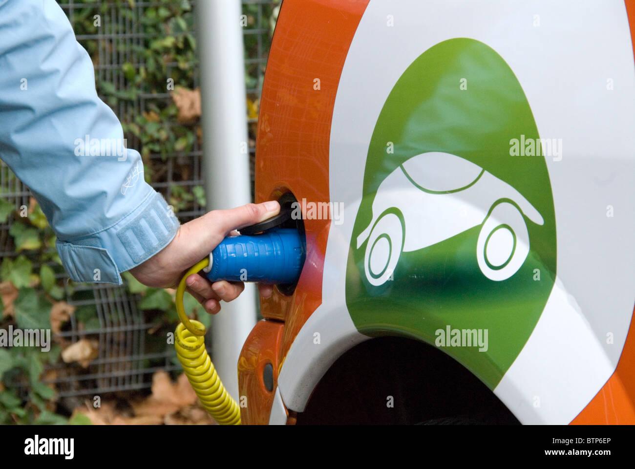 Donna collegando un auto elettrica affittati da GoGo auto elettrica EV libero Elektrobay punto carica Sainsbury's Immagini Stock