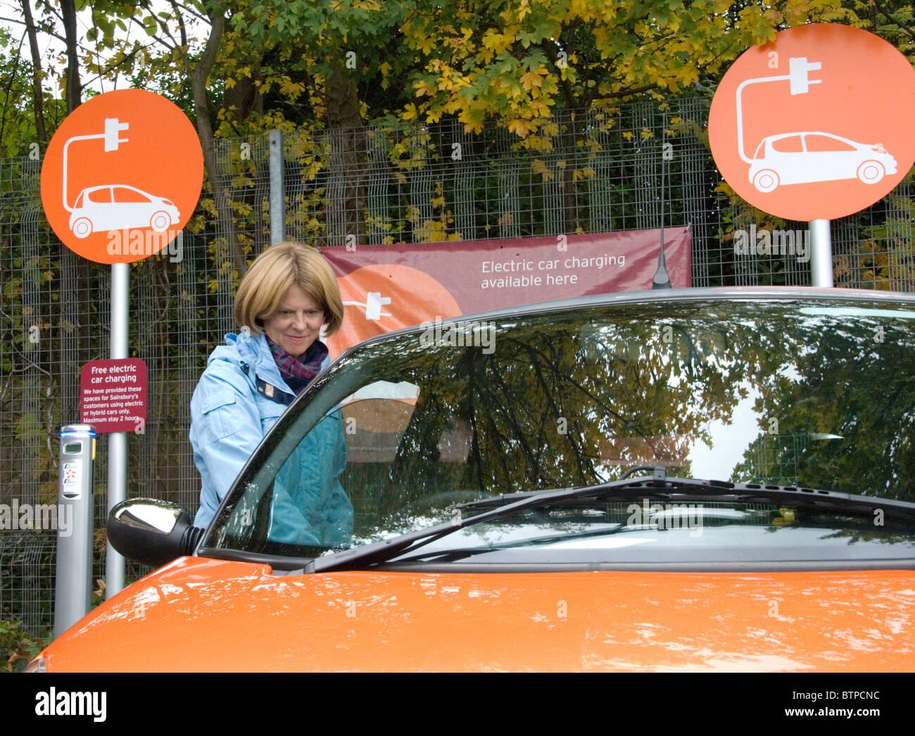 Donna salire in auto elettrica affittati da GoGo auto elettrica EV libero Elektrobay punto carica Sainsbury's Immagini Stock