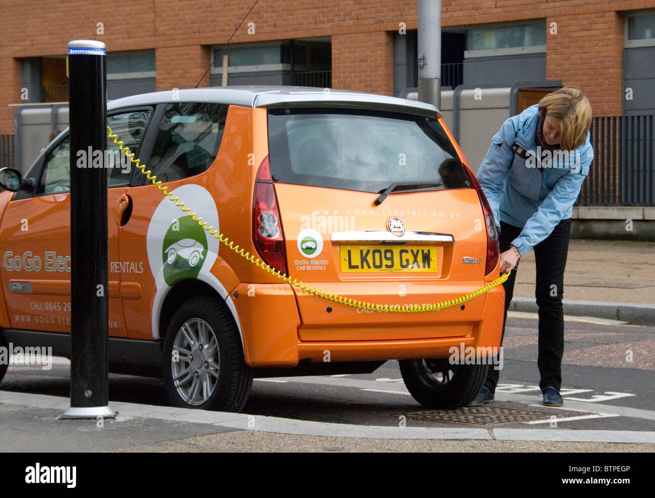 Donna intasamenti nel veicolo elettrico EV a libero parcheggio EV bay South Bank di Londra UK GoGo veicolo elettrico Immagini Stock