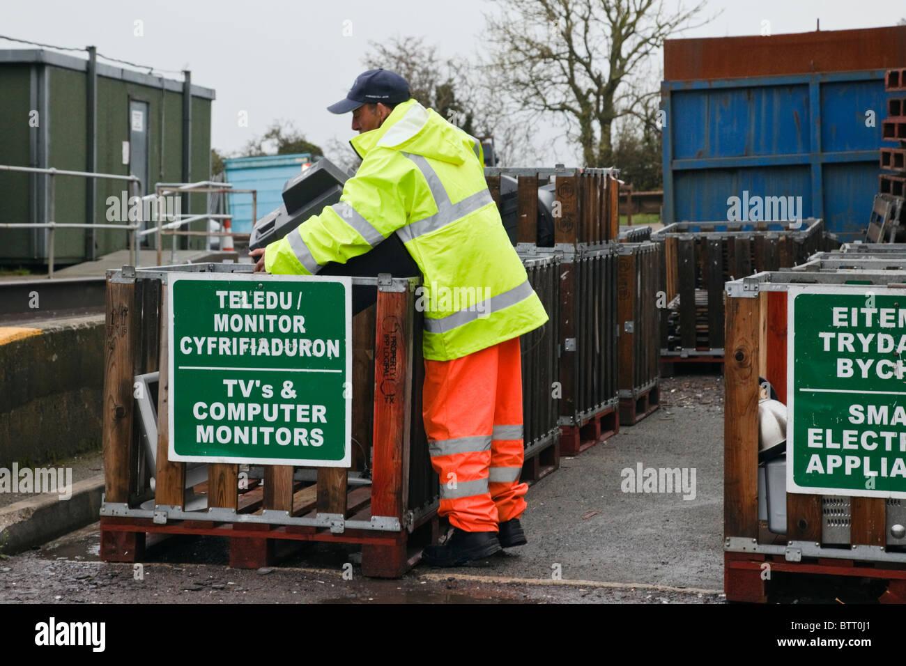 Workman disponendo di un vecchio televisore nel contenitore al consiglio di rifiutare sito per rifiuti domestici. Immagini Stock