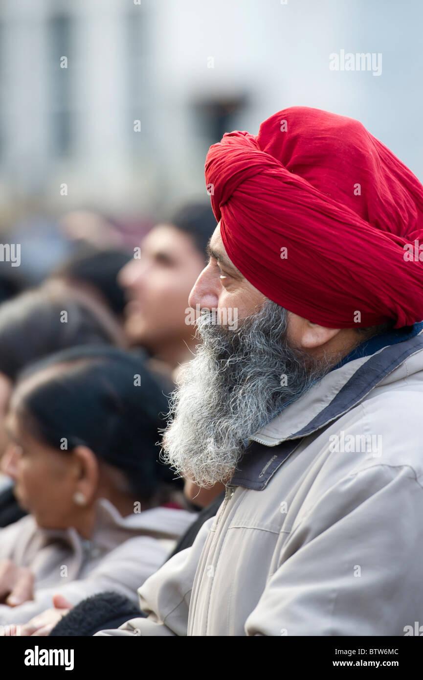 Un maschio indossa Sikh turbante rosso, ascolta attentamente per un discorso presso il Diwali Festival tenutosi Immagini Stock