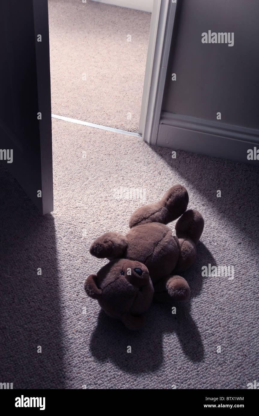 Uomo di gambe e feett passato a passo di un bambino orsacchiotto sul pavimento per lasciare la camera. Immagini Stock