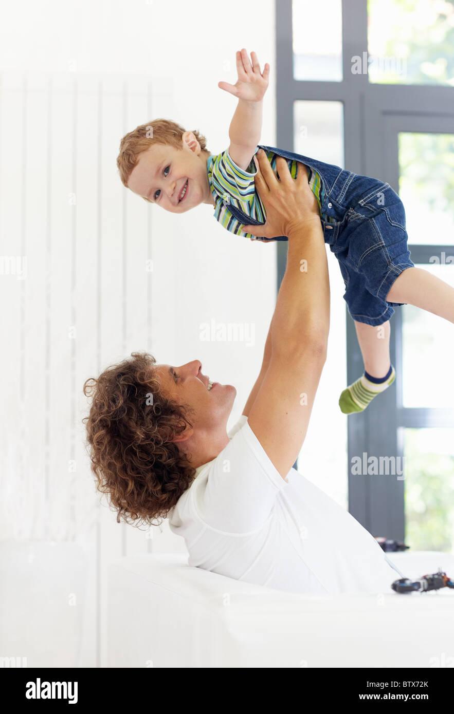 Uomo seduto sul divano e solleva il suo figlio Immagini Stock