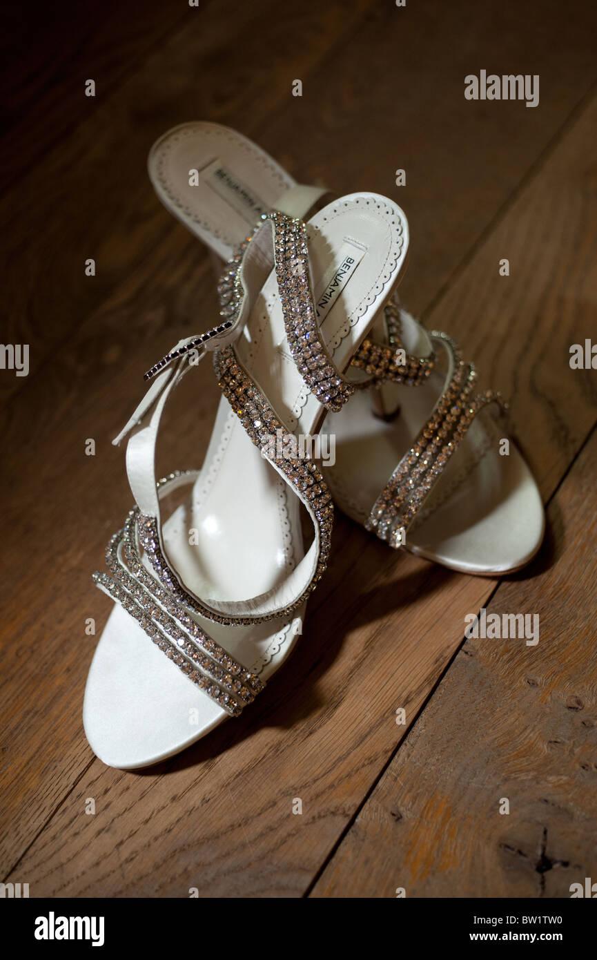 Una coppia di ladies bianco nozze diamanté scarpe in una piscina di luce su  un pavimento 766d18bff10