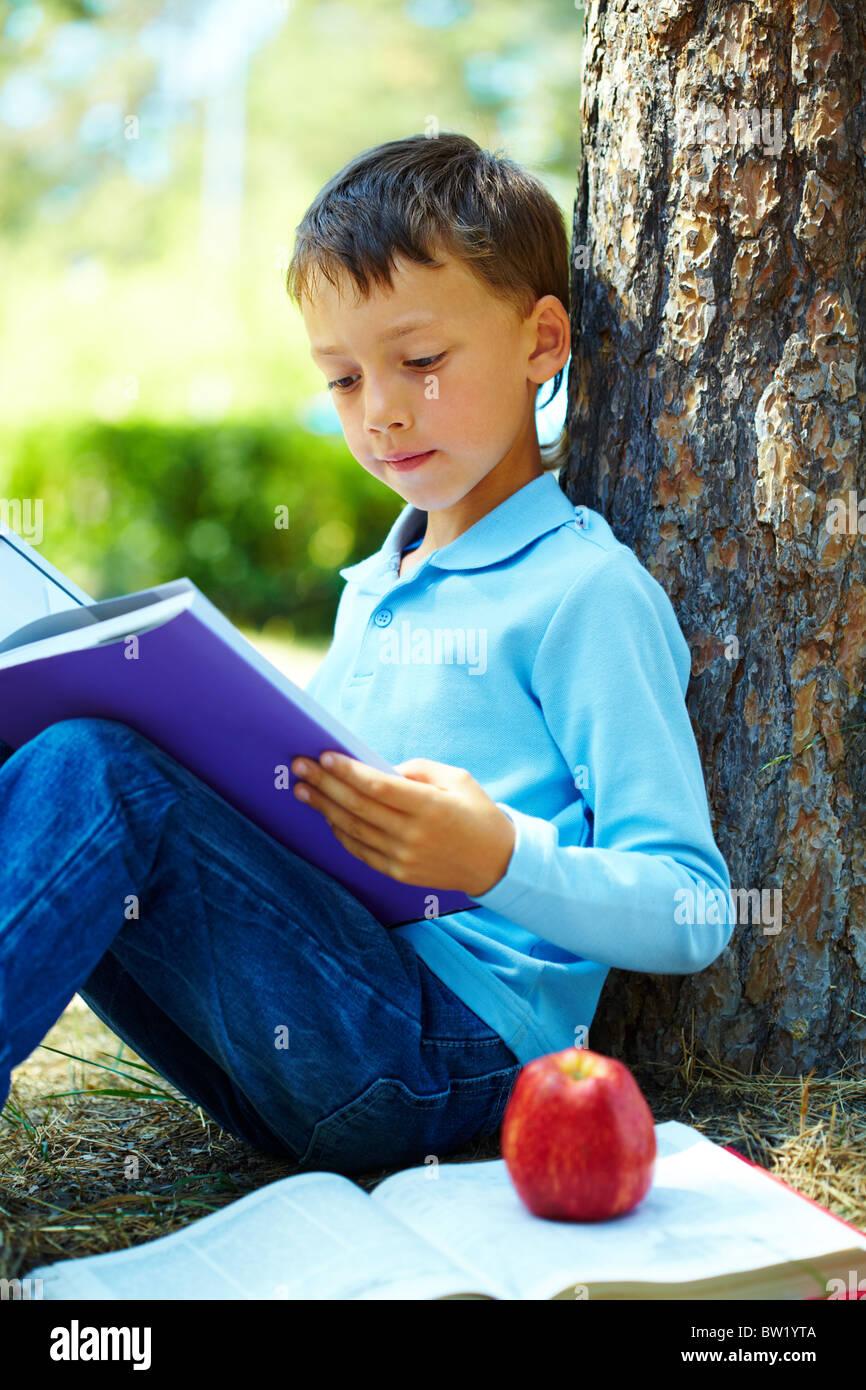 Ritratto di ragazzo intelligente nel parco e la lettura di libri interessanti nel tempo libero Immagini Stock