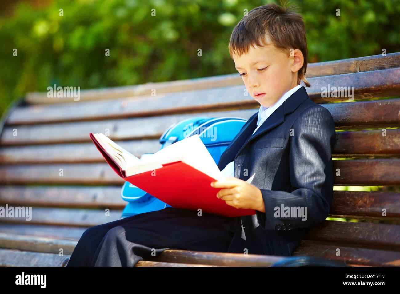 Ritratto di ragazzo intelligente seduta nel parco e la lettura di libri interessanti nel tempo libero Immagini Stock