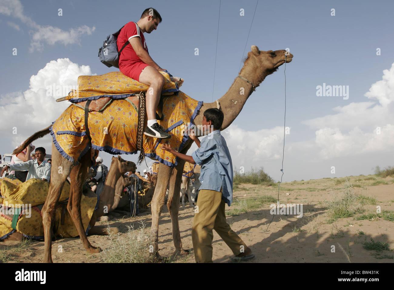 Il turista a godere di una corsa in cammello al Sam, Jaisalmer, Rajasthan, India Immagini Stock