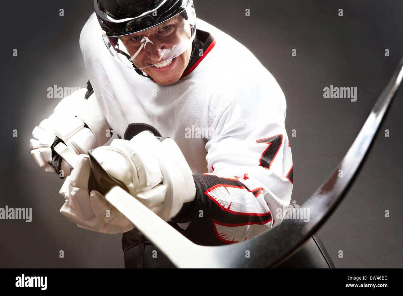 Giocatore di hockey con crudele espressione facciale pointing stick alla fotocamera Immagini Stock