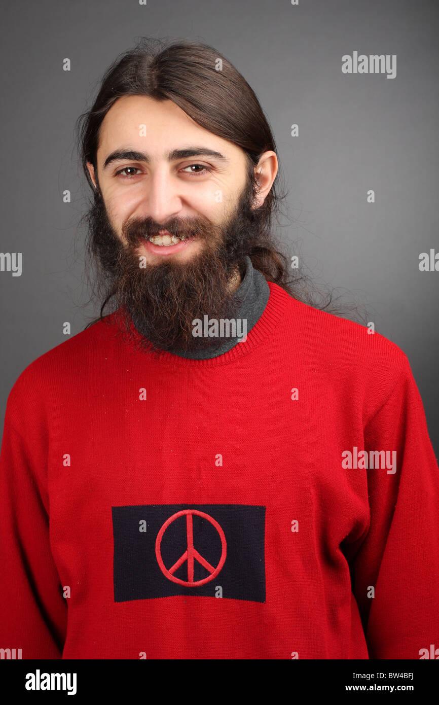 Pacifista - pace e amore, uomo sorridente con la barba nera con il simbolo della pace sul suo maglione Immagini Stock
