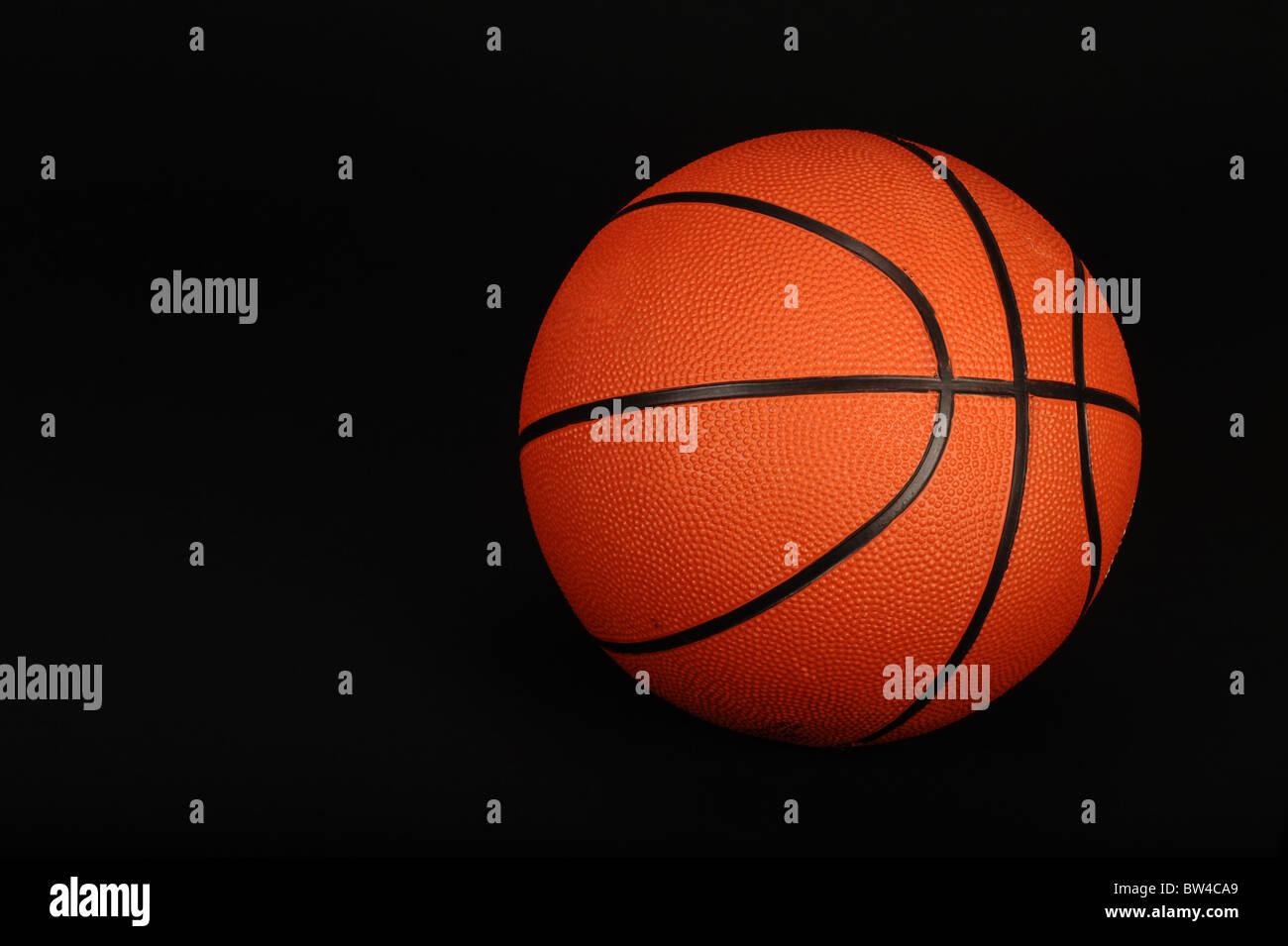 La pallacanestro su sfondo nero pronto per il tipo. Immagini Stock