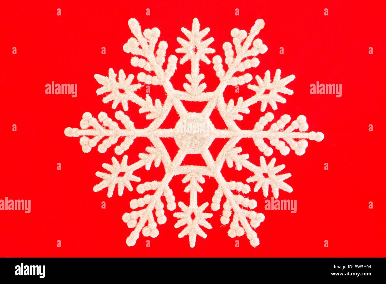 Singolo fiocco di neve bianca isolata su rosso Immagini Stock