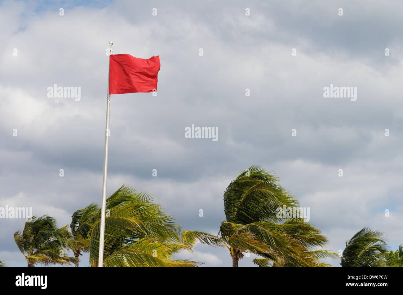 Red Flag di attenzione ad una spiaggia caraibica durante alta venti dall'uragano che si stava avvicinando Tomas Immagini Stock