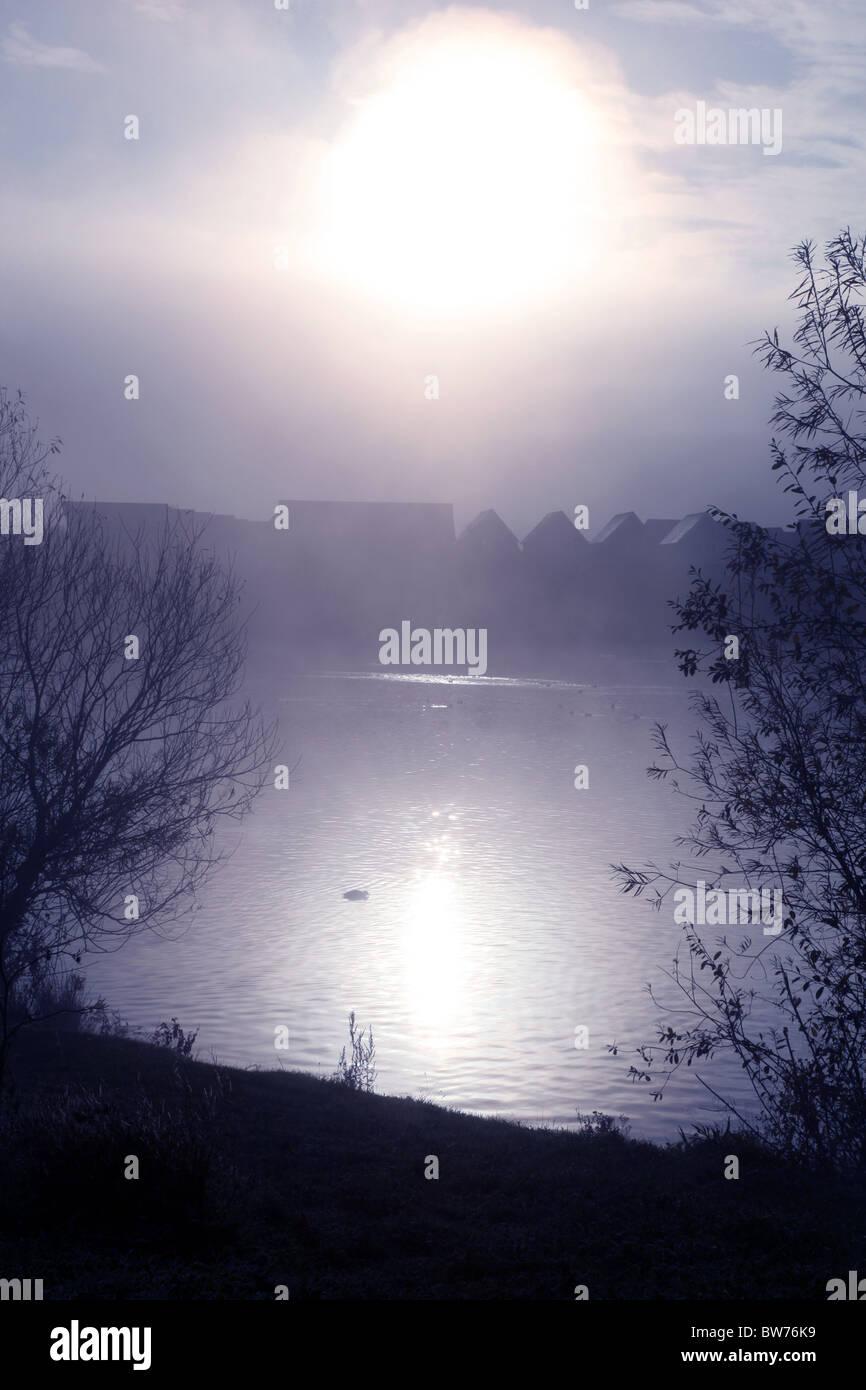 Profilo di case di distanza accanto a un lago nebbioso Immagini Stock