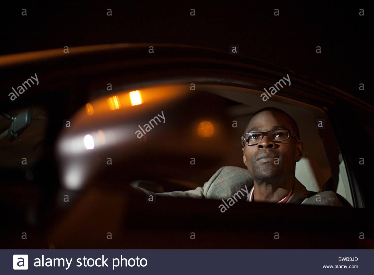 Imprenditore in macchina di notte Immagini Stock