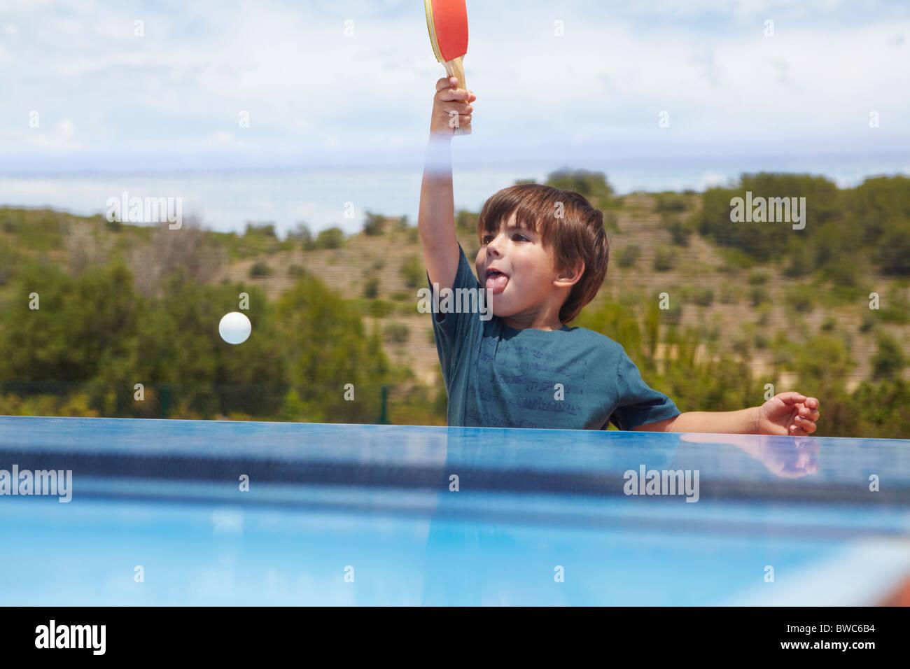 Giovane ragazzo giocando a ping-pong all'aperto Immagini Stock