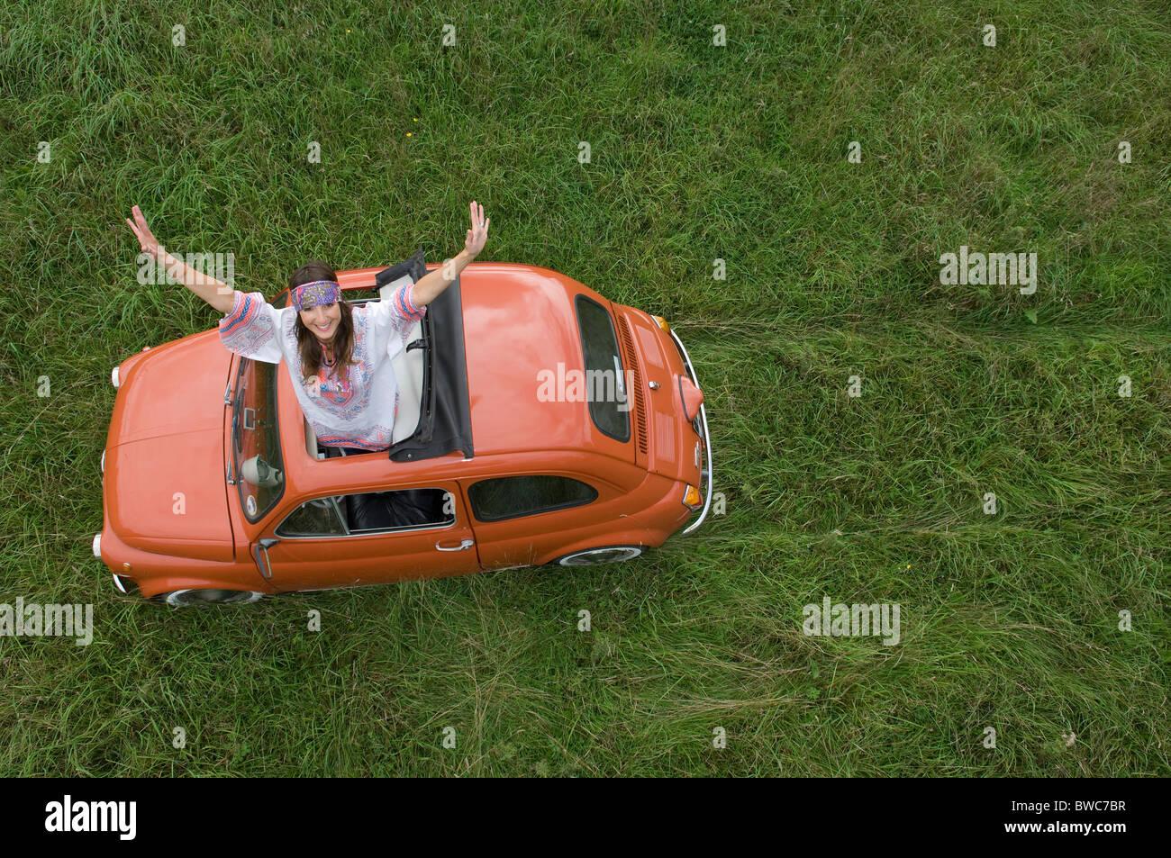 Hippy stretching femmina al di fuori della vettura Immagini Stock