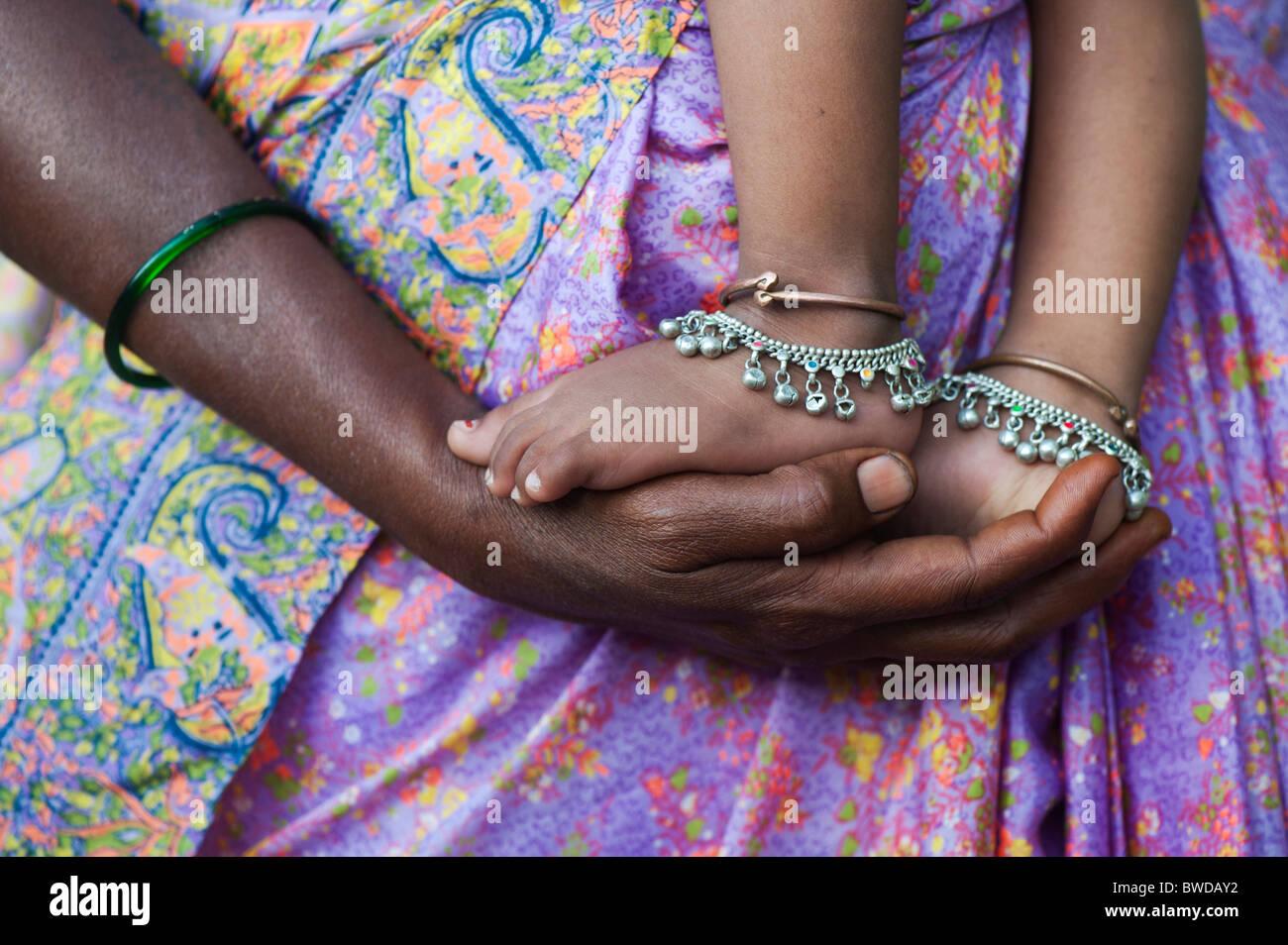 Bambini indiani piedi sulle madri le mani contro vestiti colorati. Andhra Pradesh, India Immagini Stock