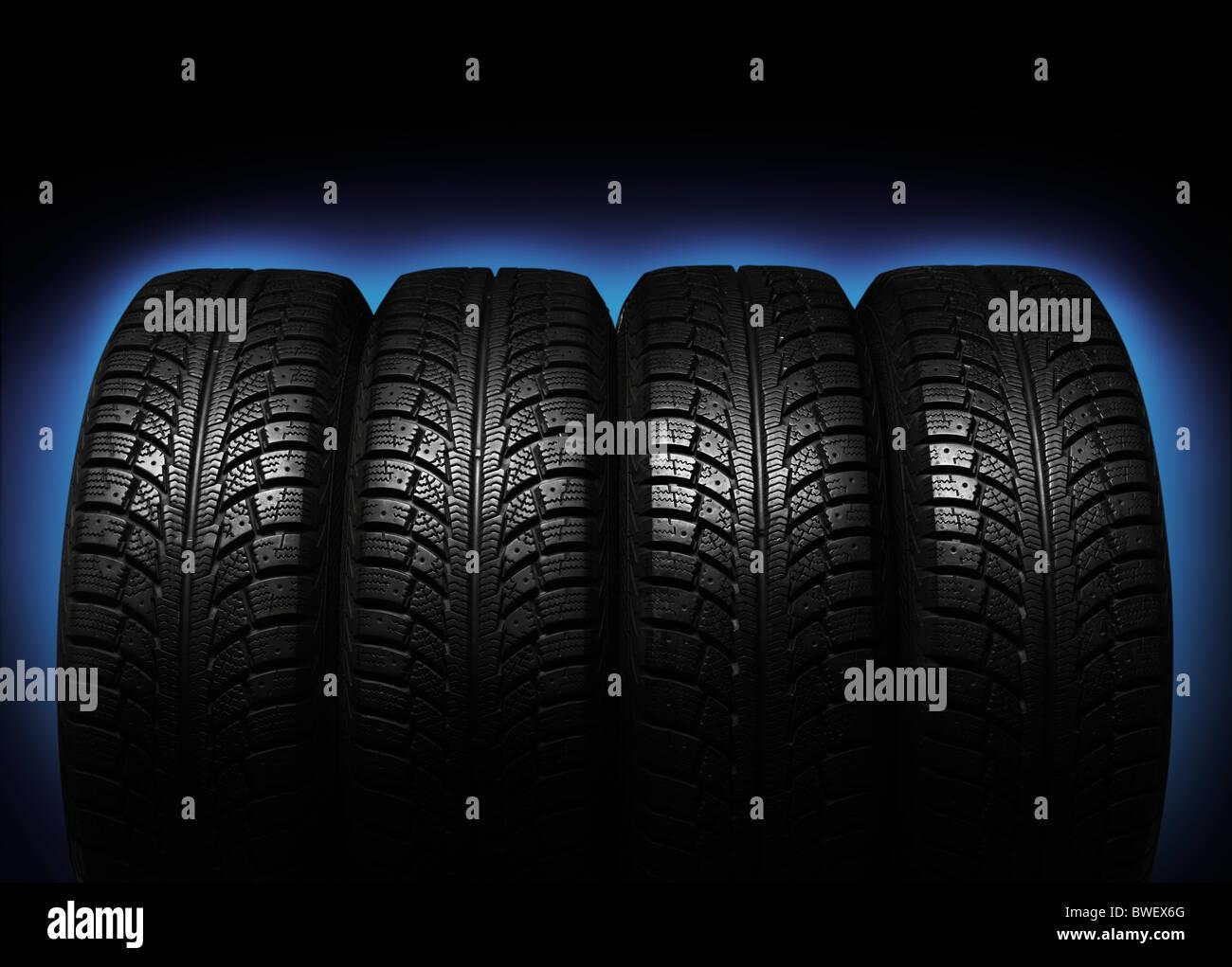 Set di quattro pneumatici invernali isolato blu su sfondo nero Immagini Stock