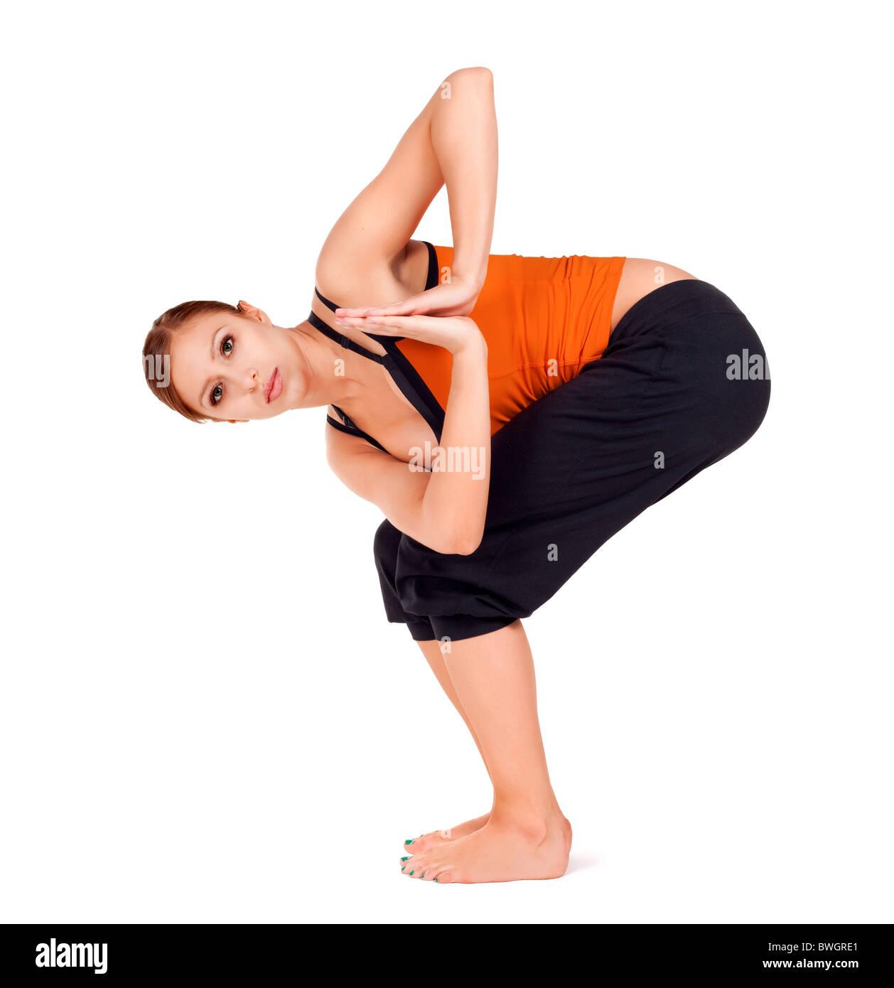 Montare la giovane donna a praticare yoga esercizio chiamato: Twisted sedia pongono nome sanscrito: Parivrtta Utkatasana Immagini Stock