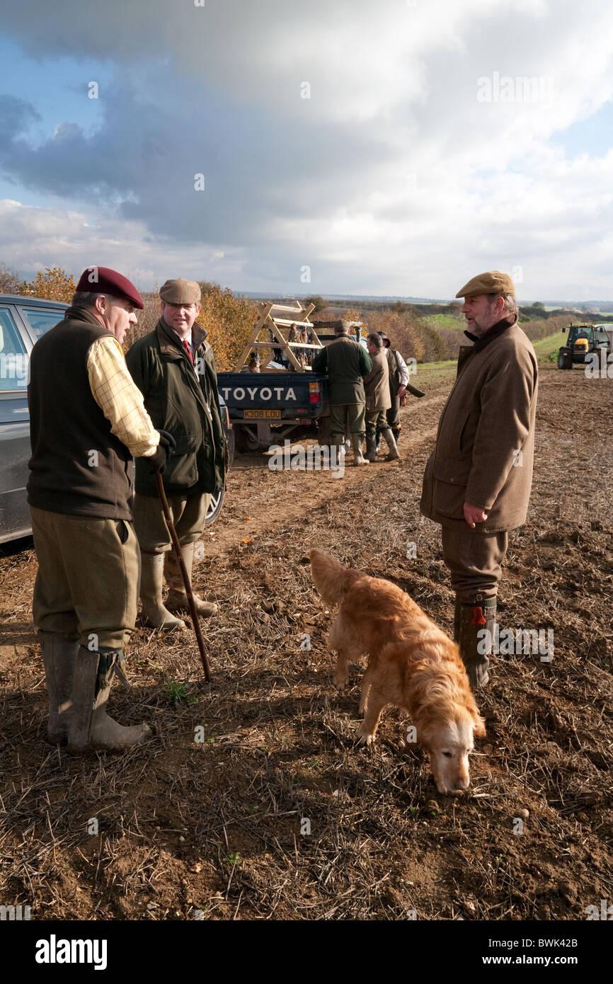 I tiratori (cannoni) discutere un gioco bird sparare con la loro gundog, Cambridgeshire East Anglia UK Immagini Stock