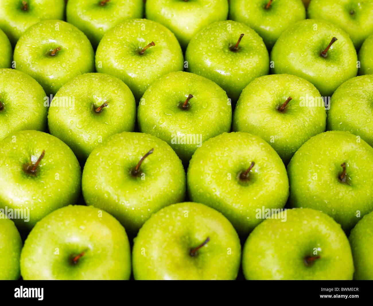 Grande gruppo di mele verdi in una fila. Forma orizzontale Immagini Stock