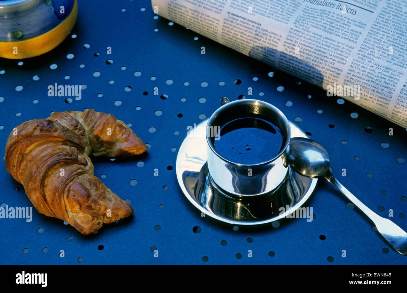 Croissant e la tazza di caffè su un tavolo con il giornale del mattino, Francia. Immagini Stock