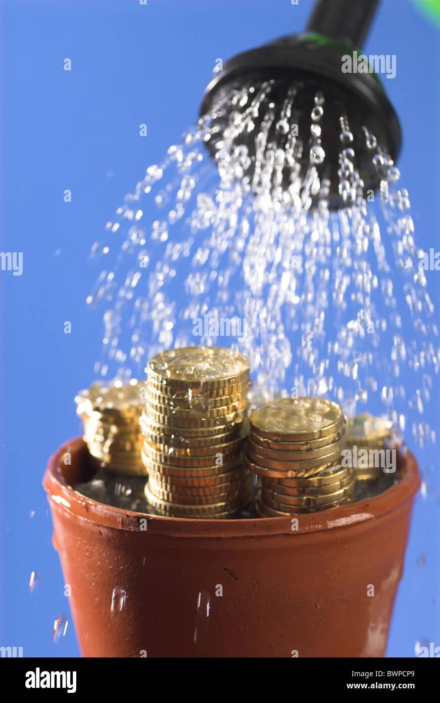 Il riciclaggio di denaro il concetto di simbolo coprivaso Monete Monete valuta doccia di acqua sotto la doccia Finanza Immagini Stock