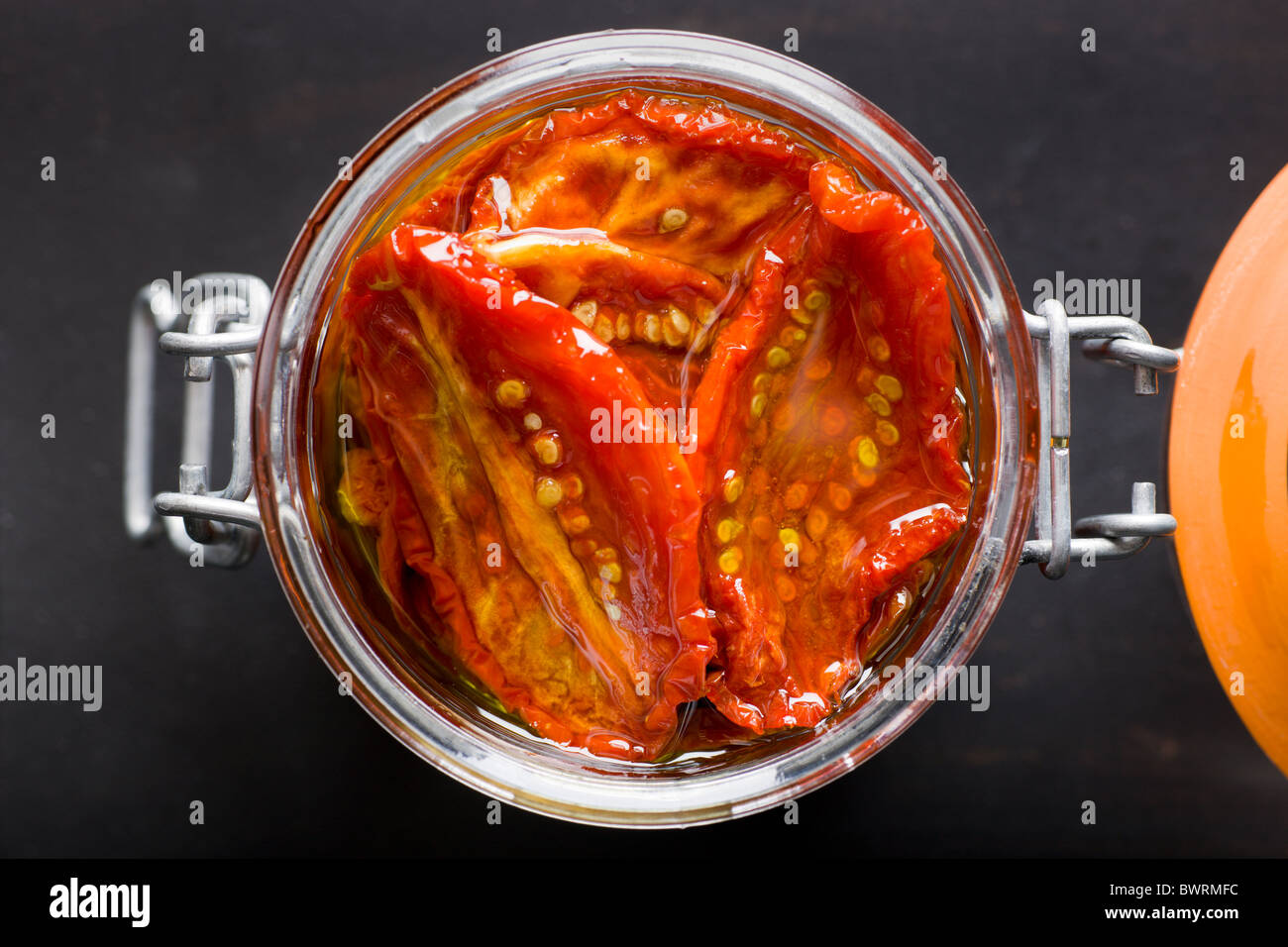 Un vaso di vetro riempito con Sun-Dried pomodori e olio di oliva su uno sfondo nero. Immagini Stock