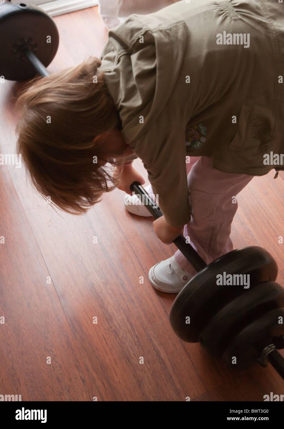 Bimba di tre anni cercando di sollevare pesi pesanti. Immagini Stock