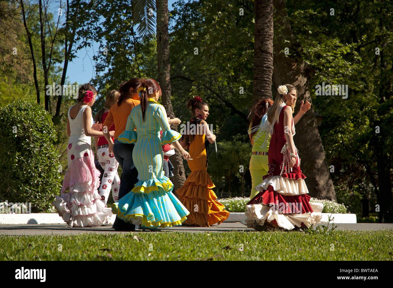 Le donne in abito di flamenco a piedi attraverso il Parco Maria Luisa verso il Siviglia Fiera di Primavera, Siviglia, Andalusia, Spagna. Foto Stock