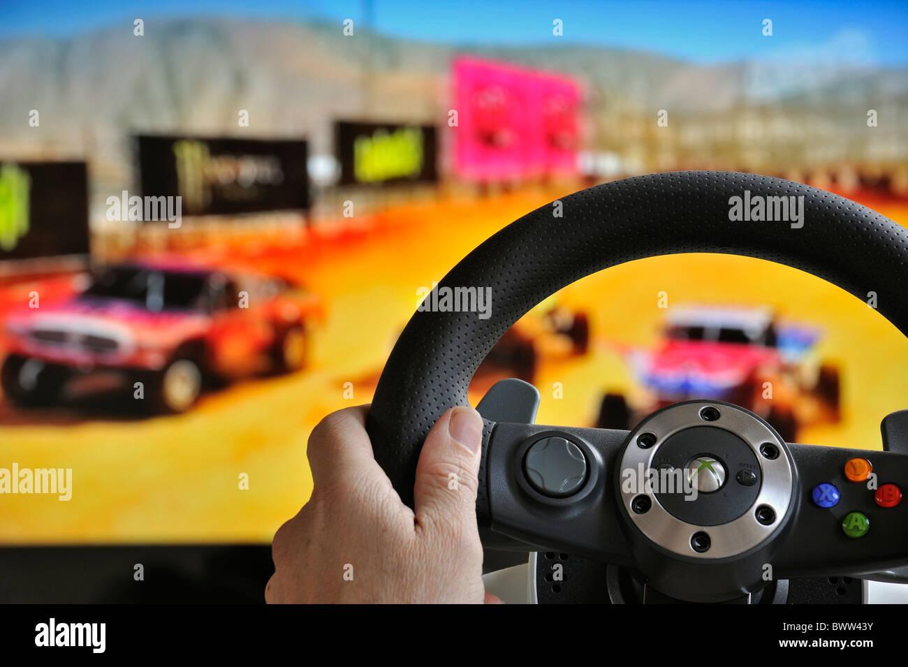 Volante controller nella parte anteriore dello schermo del televisore che mostra le vetture nel gioco di corse Immagini Stock