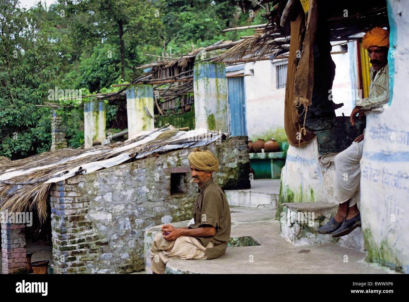 Gli uomini di religione sikh rilassante mentre avente una sigaretta al di fuori della loro casa, Mount Abu, Rajasthan, Immagini Stock