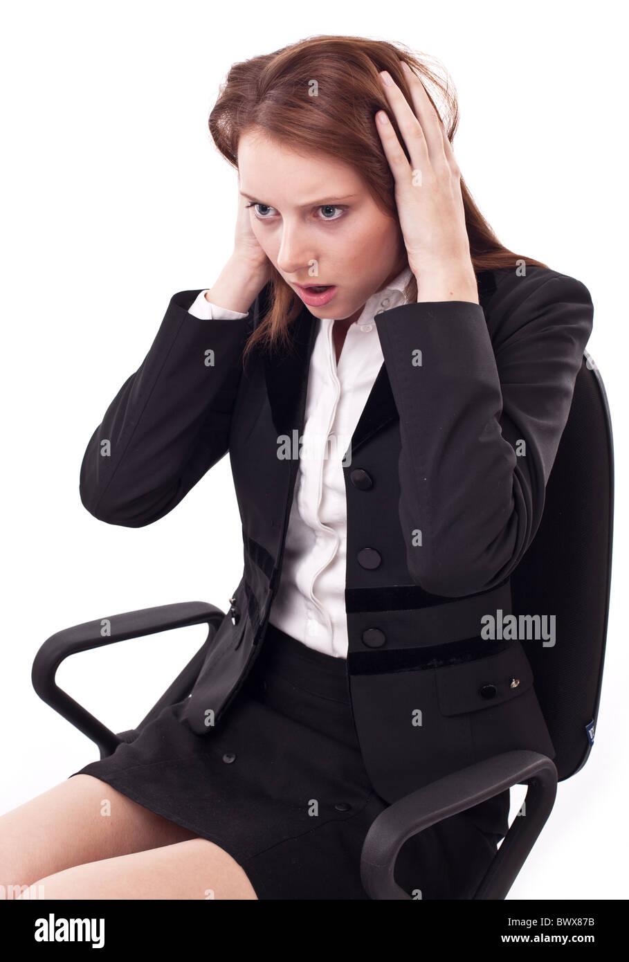 Premuto giovane donna seduta su una sedia, frizioni la sua testa. Immagini Stock