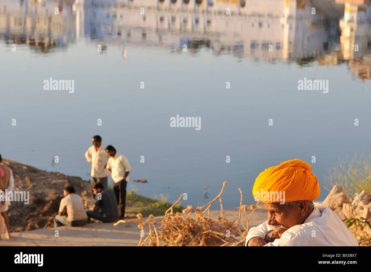 Un rajput con un luminoso turban arancione guardare i lavori in corso presso il lago di santa di Pushkar. Immagini Stock